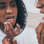 woman examines her teeth in mirror